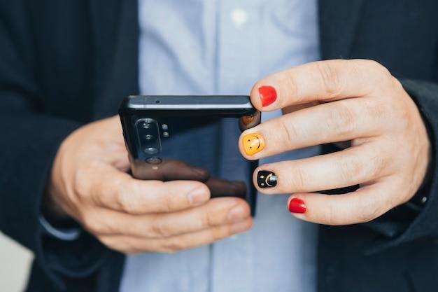 モバイルスマートフォンを使用して、モバイルアプリを介してビジネスニュースの更新とマーケティングレポートを読んで、カジュアルなビジネスマンのクローズアップ。塗られた爪を持つ男。男性の爪のデザイン。男性のマニキュア。