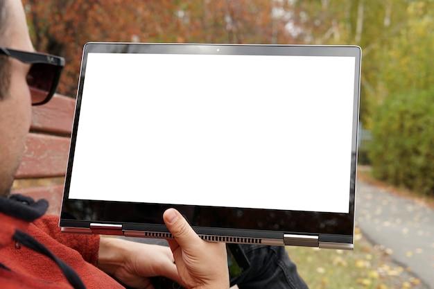 Крупный план случайного одетого молодого человека, использующего современный цифровой планшет, сидя в парке, солнечном свете. пустой белый экран монитора. молодой парень лежит в парке на скамейке и смотрит видео на компьютере. макет
