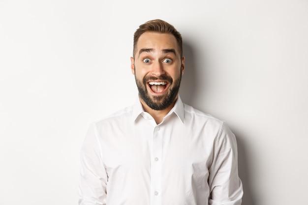 Крупный план кавказского бородатого мужчины, выглядящего возбужденным, стоящего изумленно на белом фоне.