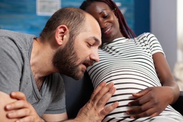 妊娠中の黒人の母親が笑っている間、腹を見て手をつないでいる子供の白人の父のクローズアップ。赤ちゃんを期待し、家でリラックスして妊娠している異人種間のカップル