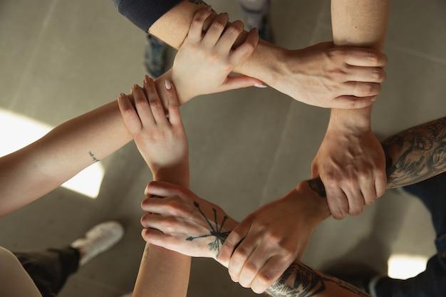 Закройте кавказских мужских и женских рук, прикрывая друг друга, трясясь. понятие о бизнесе, финансах, работе. copyspace для рекламы. образование, общение и фриланс. тимбилдинг, поддержка.