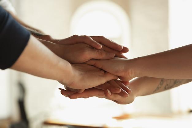Закройте кавказских мужских и женских рук, прикрывая друг друга, трясясь. понятие о бизнесе, финансах, работе. copyspace