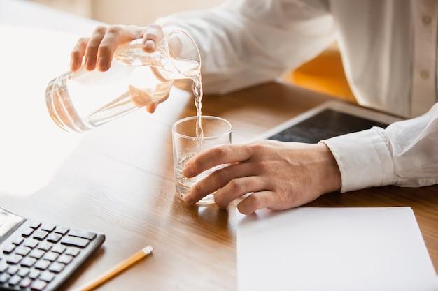 グラスに水を注ぐ白人男性の手のクローズ アップ。ビジネス、金融、仕事、オンライン ショッピング、販売のコンセプト。