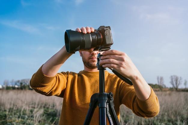 Кавказский мужчина в желтом свитере крупным планом настраивает камеру, чтобы сфотографировать вид в солнечный день