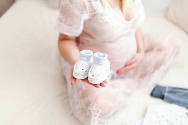 足を組んでベッドの上に座っている間片方の手で赤ちゃんの靴を保持している白人の妊娠中の女性のクローズアップ。もう一方のおなか。 Premium写真