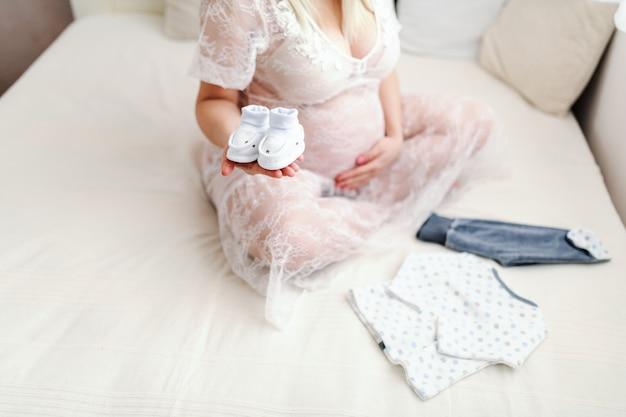 足を組んでベッドの上に座っている間片方の手で赤ちゃんの靴を保持している白人の妊娠中の女性のクローズアップ。もう一方のおなか。