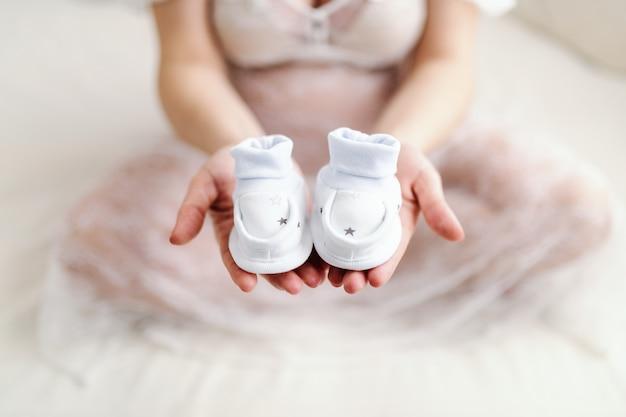 足を組んでベッドの上に座っている間片方の手で赤ちゃんの靴を保持している白人の妊娠中の女性のクローズアップ。 Premium写真