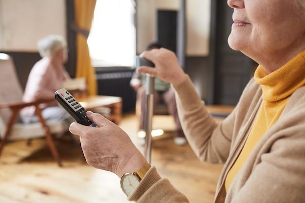 Крупным планом кавказской старшей женщины, держащей пульт во время просмотра телевизора в доме престарелых с копией пространства