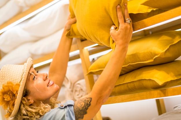 白人女性の肖像画のクローズアップは、商業センターの家の装飾店から黄色い枕を選んで取ります-ショッピングと人々のライフスタイル-ショップ活動の大人の女性