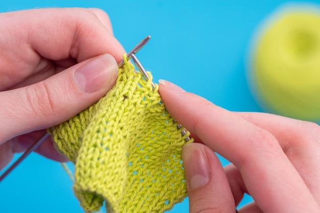 파란색 배경에 녹색 실을 뜨개질하는 백인 여성의 손을 닫습니다. 선택적 초점입니다. 공간을 복사합니다.