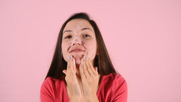 Крупным планом кавказская женщина, умывающая лицо, делая пузырьковую пену для лица и очищая кожу лица на розовом