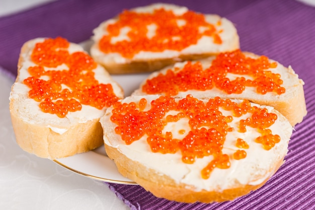 Крупный план икры, намазанной на четыре ломтика багетного хлеба, расположенных на тарелке и сидящих на фиолетовой подставке на обеденном столе
