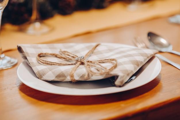 Крупный план керамической тарелки с коричневой и белой проверенной салфеткой с лентой на деревянном обеденном столе со столовыми приборами. рождественский ужин концепция.