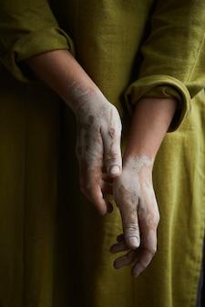 粘土の汚れた陶芸家の手のクローズアップ。陶器工房陶器を作る過程。マスター陶芸家は彼女のスタジオで働いています