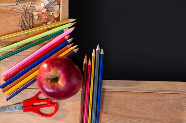 Крупным планом доске с цветными карандашами и яблоком