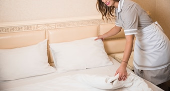 Close-up of chambermaid white bed sheet in room