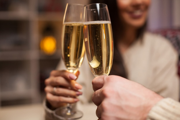 クリスマスを祝う陽気なカップルが持っているシャンパングラスのクローズアップ。
