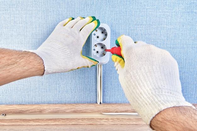 Крупным планом рабочий меняет коробку электрической розетки с помощью отвертки.