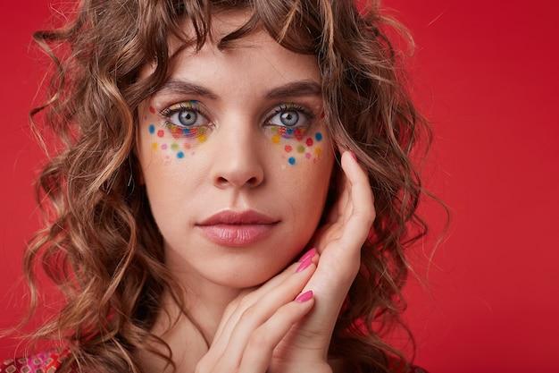 낭만적 인 헤어 스타일과 축제 메이크업이 얼굴을 몹시 만지고 부드럽고 입술을 접은 채로 보이는 매력적인 아가씨의 근접 촬영