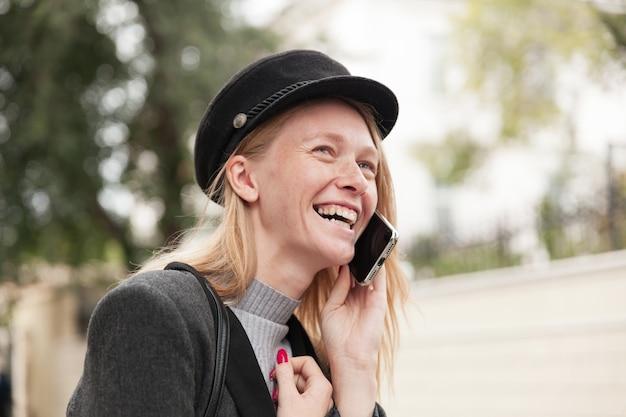 街歩き中にエレガントな暖かい服を着て、彼女の友人に電話をかけ、冗談から楽しく笑っている魅力的な若い陽気なブロンドの女性のクローズアップ