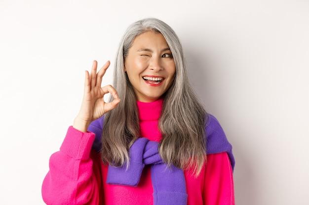 ファッショナブルなピンクのセーターで陽気なアジアの祖母のクローズアップ、まばたきと大丈夫な兆候を示して、昇進をお勧めします、白い背景の上に立っています