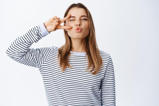 キスのための陽気なブロンドの女性のパッカーの唇のクローズアップと目の近くのvサインを示して、正面でまばたき、白い壁にカジュアルな服を着て立っている