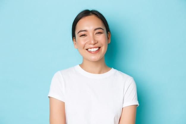 Крупный план веселой беззаботной азиатской девушки в белой футболке, широко улыбаясь.