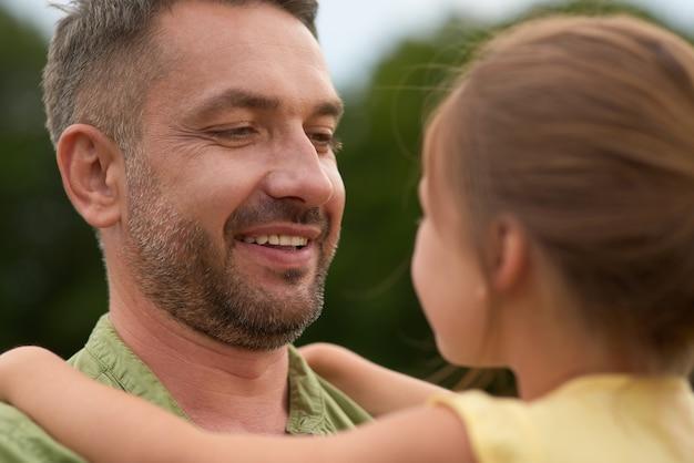 一緒に時間を過ごしている間彼女を保持している彼の小さな女の子を見ている陽気なお父さんのクローズアップ