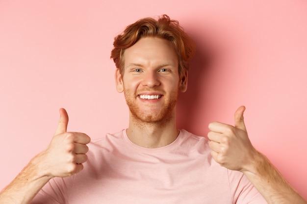 Крупным планом веселый мужчина с рыжими волосами и бородой, показывает палец вверх и улыбается, говорит да, одобряет и хвалит что-то крутое, стоя на розовом фоне.