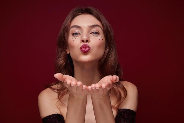 空気のキスのために唇を折りたたむ間、手のひらを上げたまま、クラレットの背景の上にポーズをとっている間、カメラを積極的に見て、お祝いのメイクアップで陽気なかなり若い茶色の髪の女性のクローズアップ