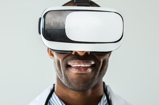 Крупным планом веселый профессиональный афро-американский док в очках vr, стоящих у белой стены