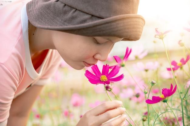 庭でコスモスの花の匂いがする陽気な女性のクローズアップ。