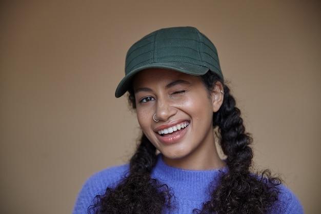 행복하게 윙크하는 어두운 피부를 가진 쾌활한 젊은 곱슬 갈색 머리 여자의 근접 촬영, 보라색 스웨터와 녹색 야구 모자에 서있는 머리띠에 그녀의 긴 머리를 유지