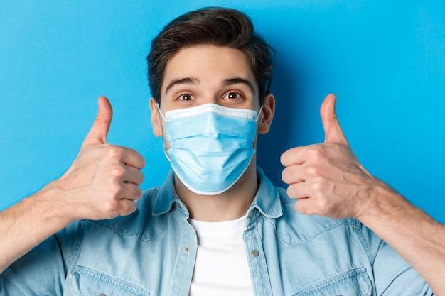 Крупный план веселого молодого человека в медицинской маске, улыбающегося, показывая большие пальцы в знак одобрения, лайкающего и согласного, стоящего над синей стеной