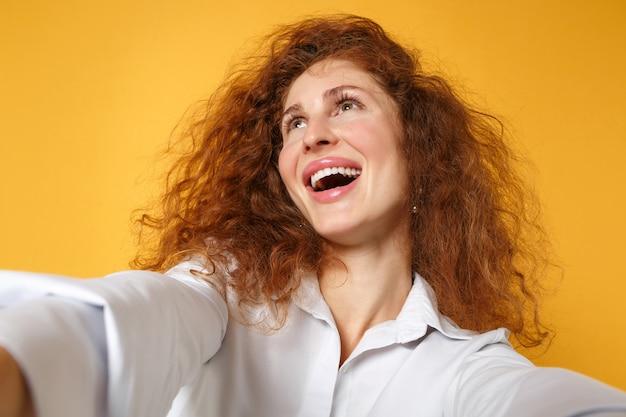 Крупным планом веселая молодая рыжая девушка в белой рубашке позирует изолированной на желто-оранжевой стене