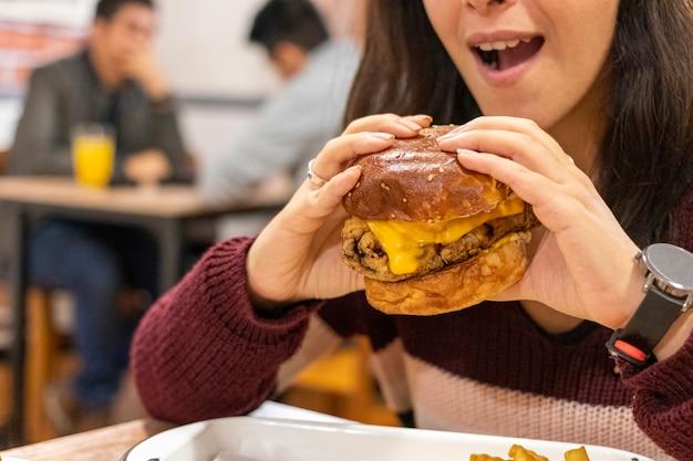 それを食べる準備ができている女性とチーズとチーズバーガーのクローズアップ