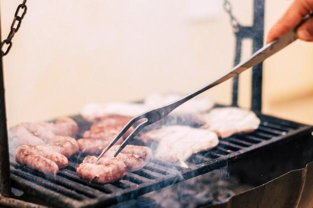 温かいグリルで肉を調理するシェフのクローズ アップ