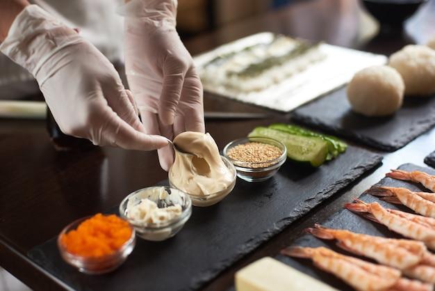 日本食を準備するシェフの手のクローズアップ。レストランで巻き寿司を作る日本人シェフ。