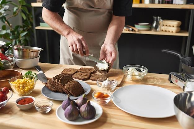 キッチンのテーブルでトースターを準備しているパンにバターを塗るエプロンのシェフのクローズアップ