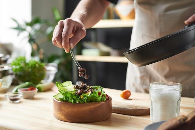 그는 요리사에서 요리 요리 야채와 함께 접시에 튀긴 고기를 넣어 요리사의 근접