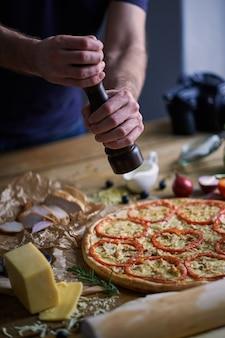 イタリアのピザを塩漬けにするシェフの手のクローズアップ。テーブルの上のさまざまな材料。認識できない