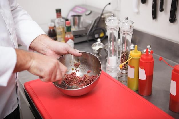 Крупным планом руки повара, помешивая нарезанную говядину для тартара в металлической миске