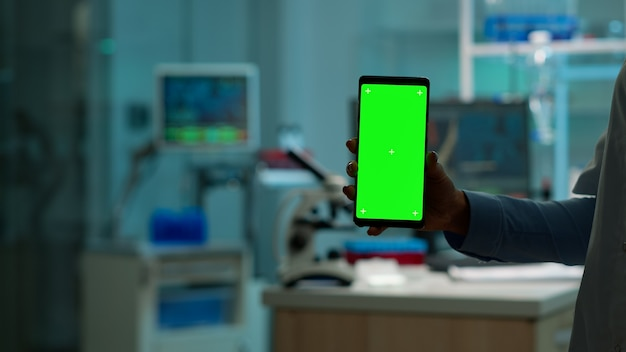 간호사가 혈액 샘플을 가져오는 동안 생물학 실험실에 녹색 스크린이 서 있는 스마트폰을 들고 있는 화학자의 손을 닫습니다. 모형, 크로마 키 디스플레이가 있는 스마트폰을 사용하는 과학자