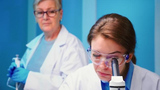 顕微鏡を使用して科学設備の整った実験室で働く化学者女性医師のクローズアップ