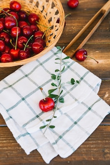 Close-up of chequered pattern napkin and red cherries in wicker bowl