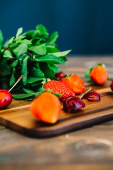 Close-up of cherries and strawberries on cutting board in front of mint leaves
