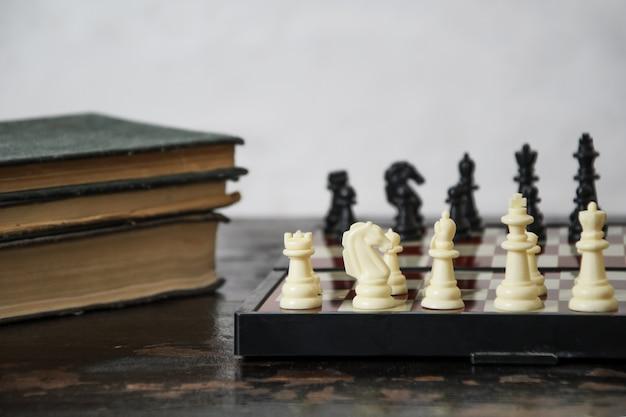 ゲームの開始時にチェス盤に置かれたチェスの駒と古い本のスタックのクローズアップ
