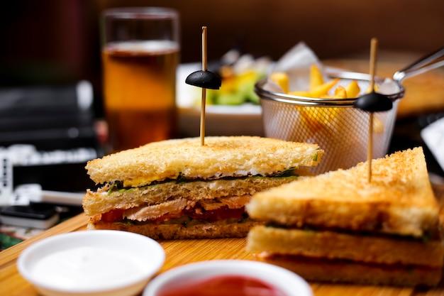 Крупный план сэндвича с курицей и томатным огурцом с майонезом и солеными огурцами, подается с картофелем фри