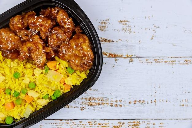 플라스틱 쟁반에 쌀과 달콤하고 신 소스에 치킨 데리야끼 닫습니다. 평면도.