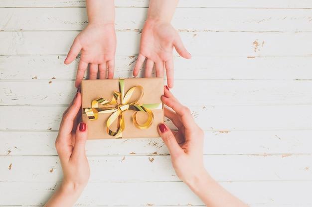 나무 배경 위에 선물 상자를 들고 아이와 어머니 손을 닫습니다.